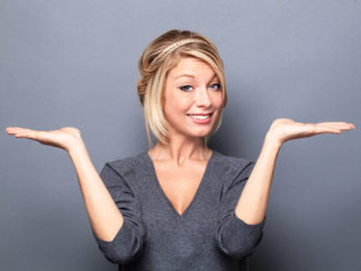 Eine junge Dame mit blonden Haaren steht vor einem dunkelgrauen Hintergrund und wirkt unentschlossen