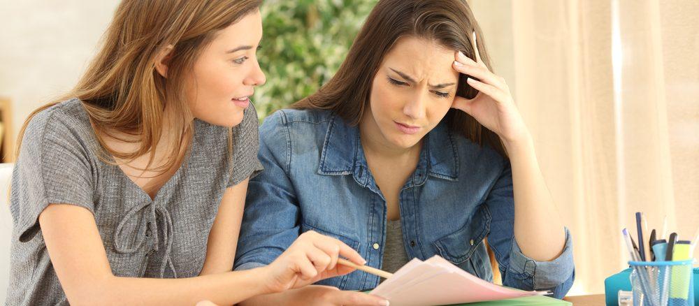 Zwei junge Damen sitzen am Tisch und halten Zettel in der Hand.