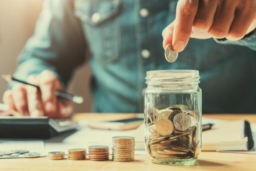 Jemand füllt ein Glas mit Münzen und bedient einen Taschenrechner