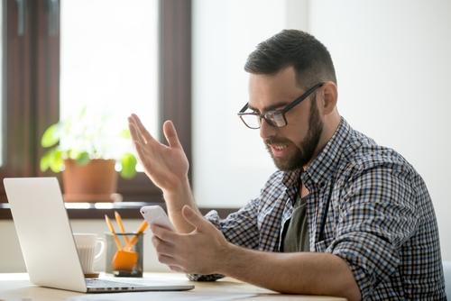 Ein junger Mann sitzt vor seinem Notebook und ärgert sich über einen unerwünschten Anruf