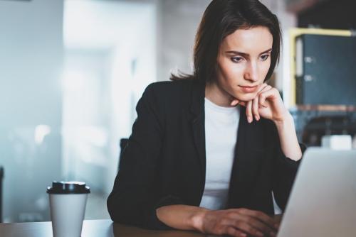 Eine junge Frau mit dunklen Haaren sitzt vor dem Notebook und hat einen Kaffee-Becher auf dem Tisch