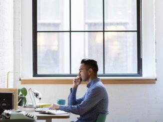 Ein junger Mann in blau kariertem Hemd sitzt an seinem Arbeitsplatz vor dem Notebook. Im Hintergrund ist ein großes Fenster.