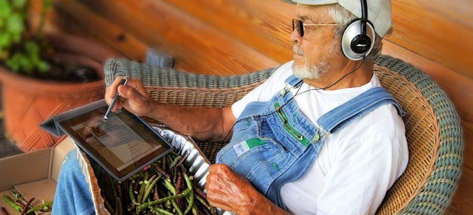 Ein älterer Mensch bzw. Mann sitzt auf einem Stuhl und trägt Kopfhörer