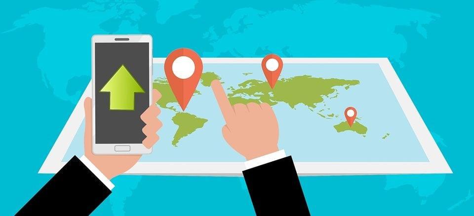 Jemand hält ein Smartphone in der Hand und zeigt auf eine Landkarte