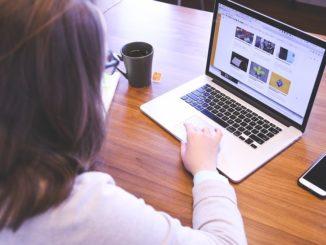 Eine Frau mit Brille tipp am Notebook etwas ein. Das Notebook ist weiß und steht auf einem Tisch.