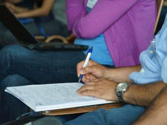 Ein Mann hält einen Schreibblock in der Hand und schreibt etwas auf.