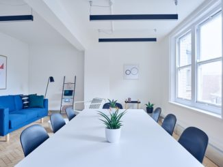 Ein weißer Konferenztisch mit blauen Stühlen und großen Fenstern.