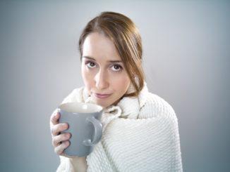 Ein junges Mädchen mit Schal um den Hals und einer blauen Tasse in der Hand