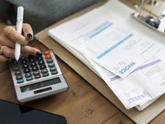 Eine junge Frau schreibt Rechnungen und nutzt dabei den Taschenrechner.
