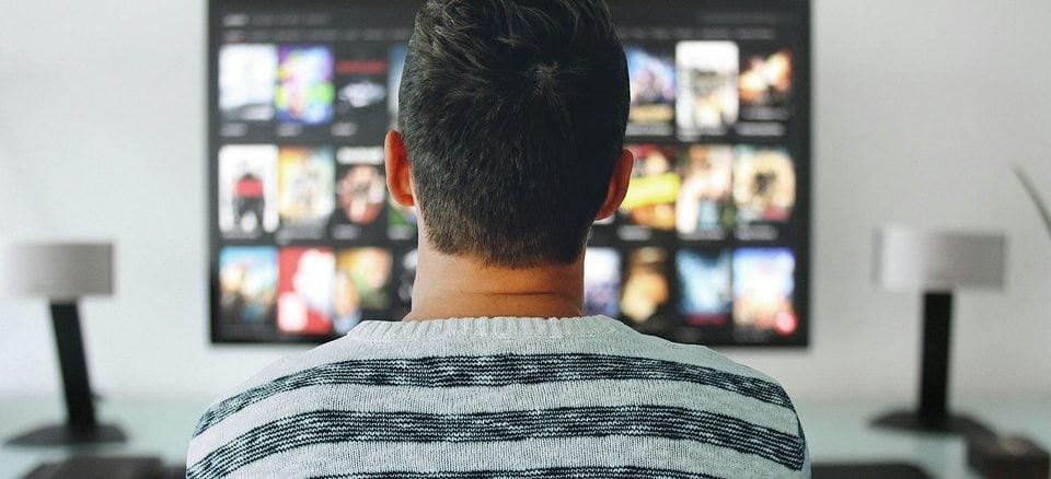 Ein junger Mann mit schwarzen Haaren sitzt vor dem TV