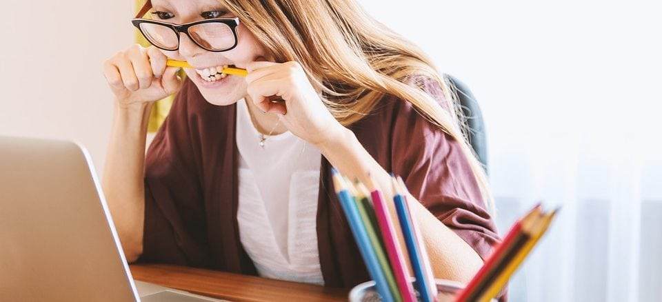 Eine junge Frau mit Brille beißt auf einen Stift und sitzt vor einem Notebook