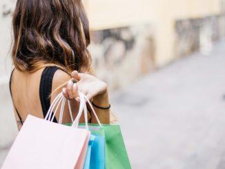 Eine junge Dame hält Einkaufstaschen in verschiedenen Farben in der Hand.