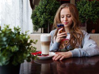 Ein junges Mädchen guckt auf ihr Smartphone und vergleicht die Tarife verschiedener Handyanbieter
