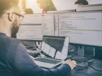 Ein junger Mann, vermutlich Softwareprogrammierer, sitzt vor einem Notebook mit zwei externen Bildschirmen