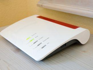 Ein Fritzbox Router in rot-weiß stecht auf einem Podest aus Holz.