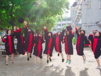 Jugendliche Absolventen springen in die Luft.