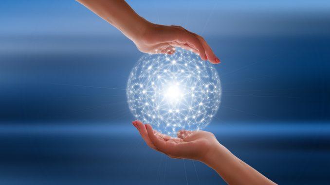 Zwei Hände halten eine weiße Kugel vor blauem Hintergrund