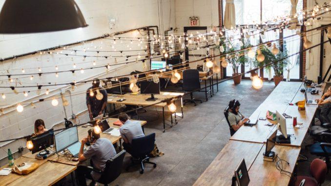 Ein Großraumbüro mit vielen Angestellten und heller Beleuchtung