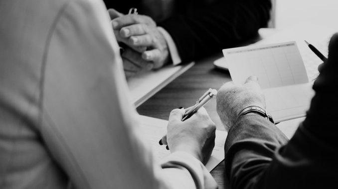 Mehrere Geschäftsleute sitzen gemeinsam an einem Tisch