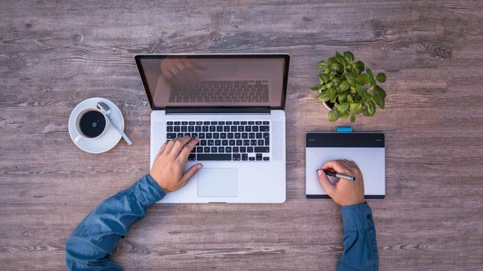 Ein Grafiker sitzt am Notebook und bedient gleichzeitig ein Grafiktablett