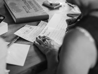 Frau sitzt am Tisch und schreibt Briefe