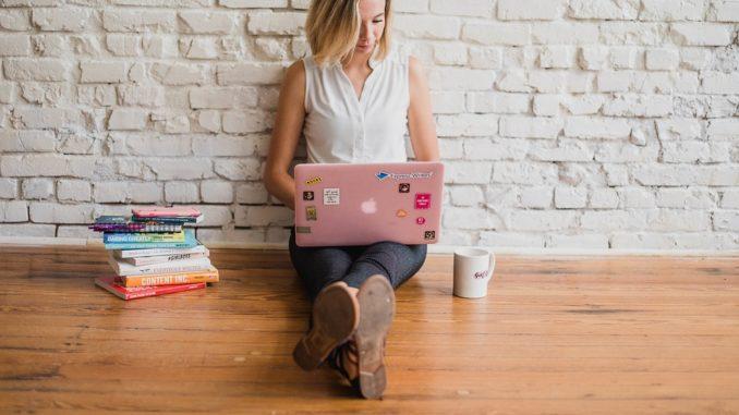 Eine junge Frau sitzt auf dem Boden und bedient ihr rosa Notebook