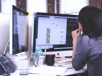 Frau sitzt am Schreibtisch und schaut auf den Bildschirm