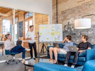 Vier junge Männer sitzen in einer Agentur und schauen auf ein Whiteboard