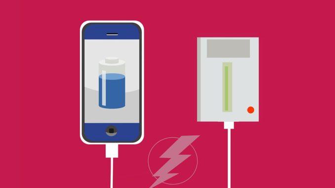 Eine Powerbank und ein Smartphone auf pinkem Hintergrund