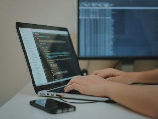 Ein Programmierer sitzt an seinem Notebook und schreibt am Quelltext