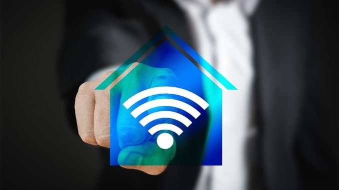 Ein Finger zeigt auf ein blaues Haus mit WLAN-Symbol