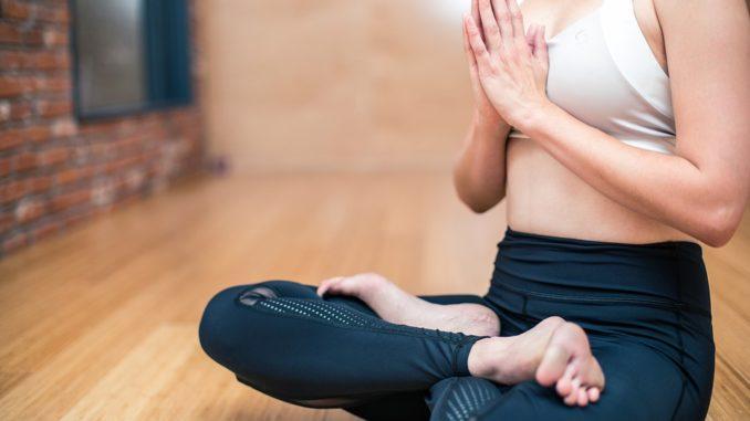 Eine junge Frau macht Yoga Übungen im Schneidersitz