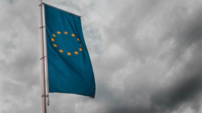 Eine blaue gelbe Fahne der europäischen Union weht im Wind vor dunklen Wolken
