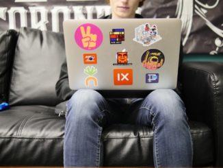 Ein junger Mann sitzt auf einer schwarzen Couch, mit dem Notebook auf den Knien.