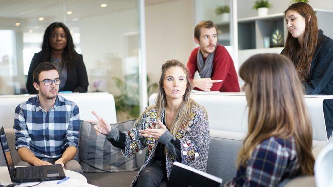 Junge Damen und Herren sitzen zusammen und kommunizieren