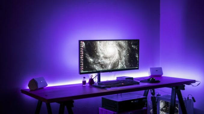 Gaming Tisch lila beleuchtet mit Monitor an.