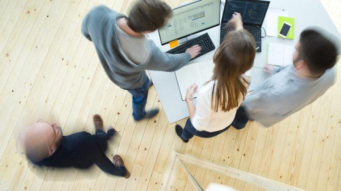 Junge Menschen stehen vor einem Tisch an einem Laptop