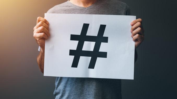 Ein schwarzes Hashtag auf einem weißen Schild