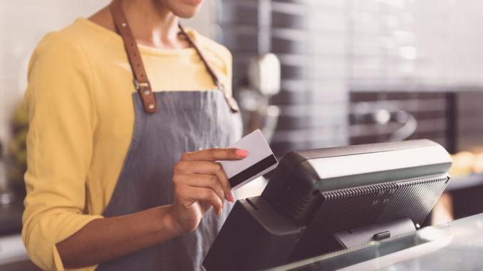 Eine Dame in gelbem Pullover steht vor einer Kasse und nimmt eine Zahlung via Kreditkarte entgegen
