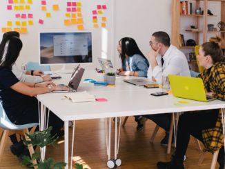 Fünf junge Menschen sitzen an einem großen weißen Team-Schreibtisch zusammen