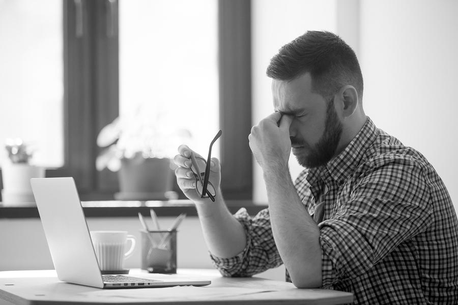 Ein junger Mann sitzt vor seinem Notebook und wirkt gestresst.