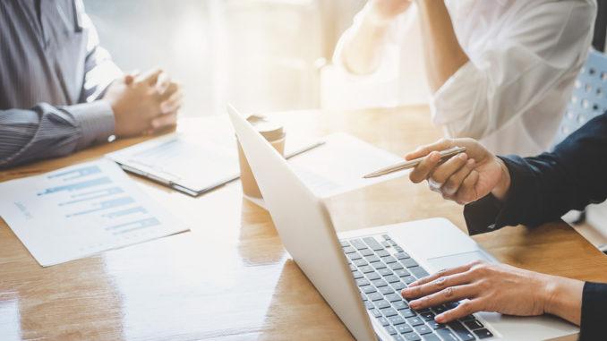 Ein Team von drei Leuten sitzt am Tisch und schaut sich etwas auf dem Notebook an