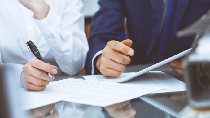 Zwei Geschäftsleute sitzen vor einem Dokument und unterschreiben es