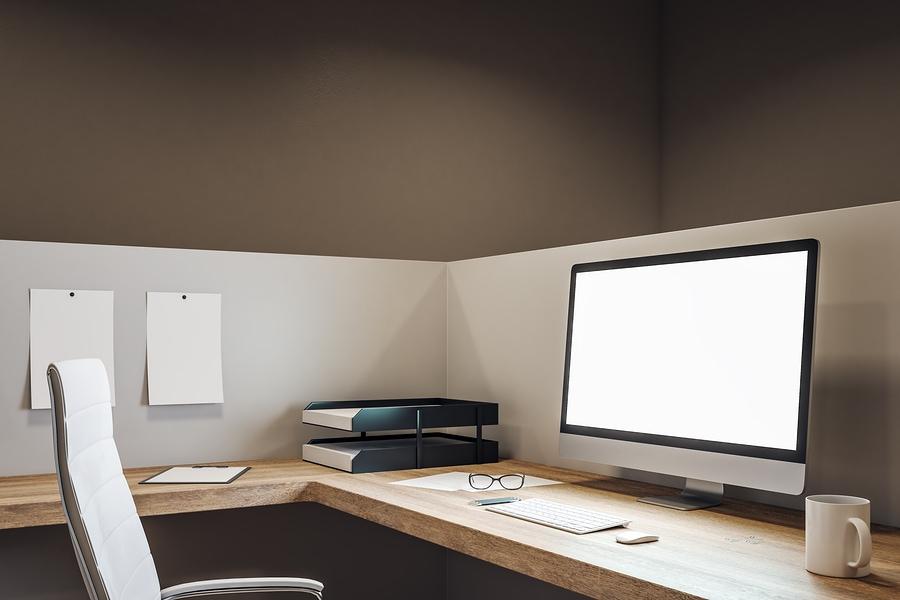 Aufgeräumtes Büro mit Trennwänden und leuchtenen Monitor.