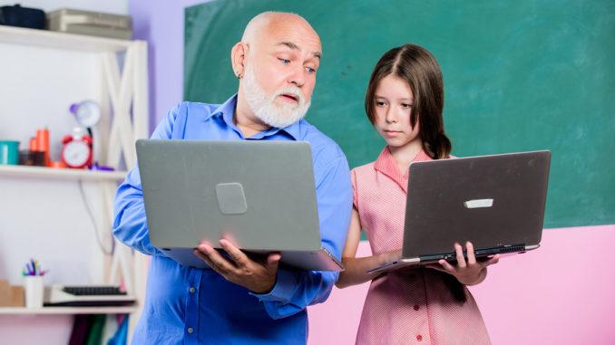 Zurück zur Schule. Kind unterrichten. Internet-Kurse. Moderne Schule. Moderner Pädagoge. Lehrer helfen Schulmädchen. Kleines Mädchen mit Manntutor-Studiengrifflaptop. Online-Unterricht. Lehrer für digitale Wissenschaft