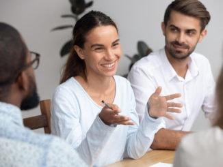 Glücklicher Frauenführertrainermentor, der mit Angestellten bei der Sitzung spricht