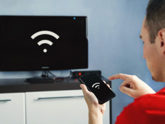 Konnektivität zwischen Smart-TV und Smartphone über WLAN-Verbindung. Steuern Sie Ihren Fernseher mit Ihrem Smartphone. Das WLAN-Symbol auf dem Telefonbildschirm und dem Monitor