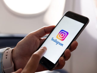 Smartphone liegt in Händen und zeigt Instagramladebildschirm an.