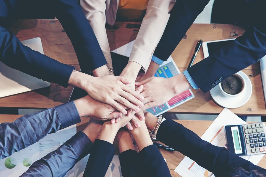 Teamwork Erfolg. Draufsichtexekutivgeschäftsleute gruppieren das Team, das glücklich ist, Teamwork zeigend und sich Händen anschließend, nachdem sie Partnergeschäft im Büro getroffen haben. Unternehmenskonzept.