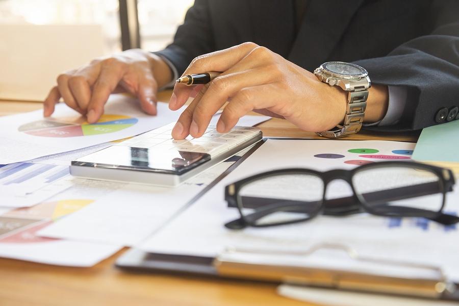 Geschäftsmann mit Luxusuhr am Handgelenk zeichnet Grafiken am Schreibtisch